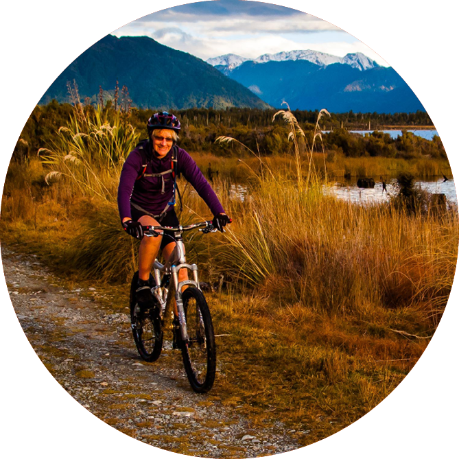 A woman smiling riding her bike through beautiful landscape